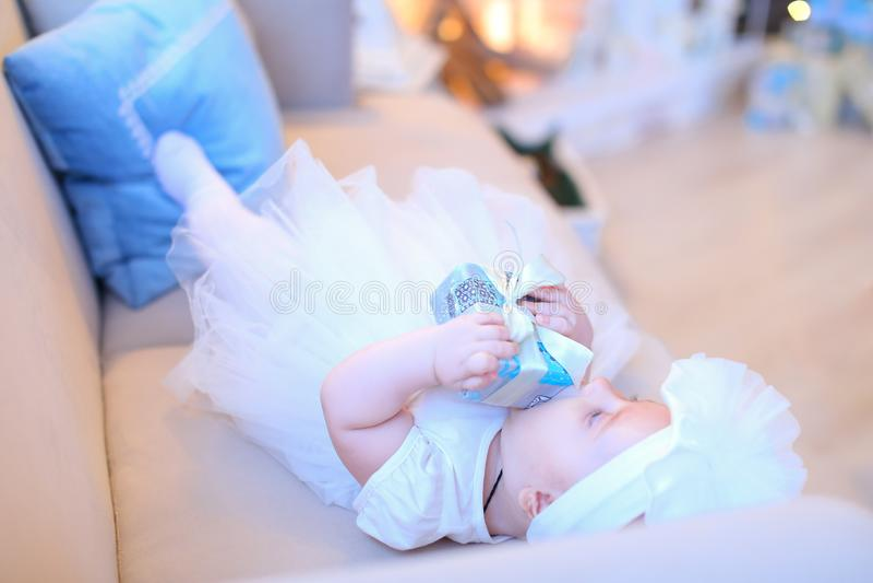 Λίγο θηλυκό μωρό που βρίσκεται στον καναπέ και που φορά τα άσπρα ενδύματα στοκ εικόνα