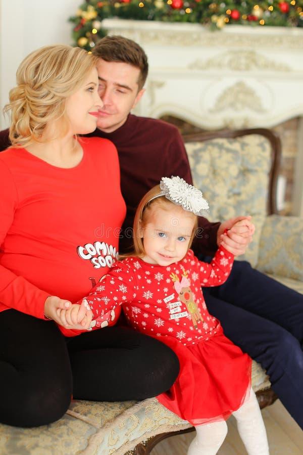 Λίγο θηλυκό παιδί που φορά την κόκκινη συνεδρίαση φορεμάτων με τον πατέρα και την έγκυο μητέρα πλησίον η εστία στοκ εικόνα