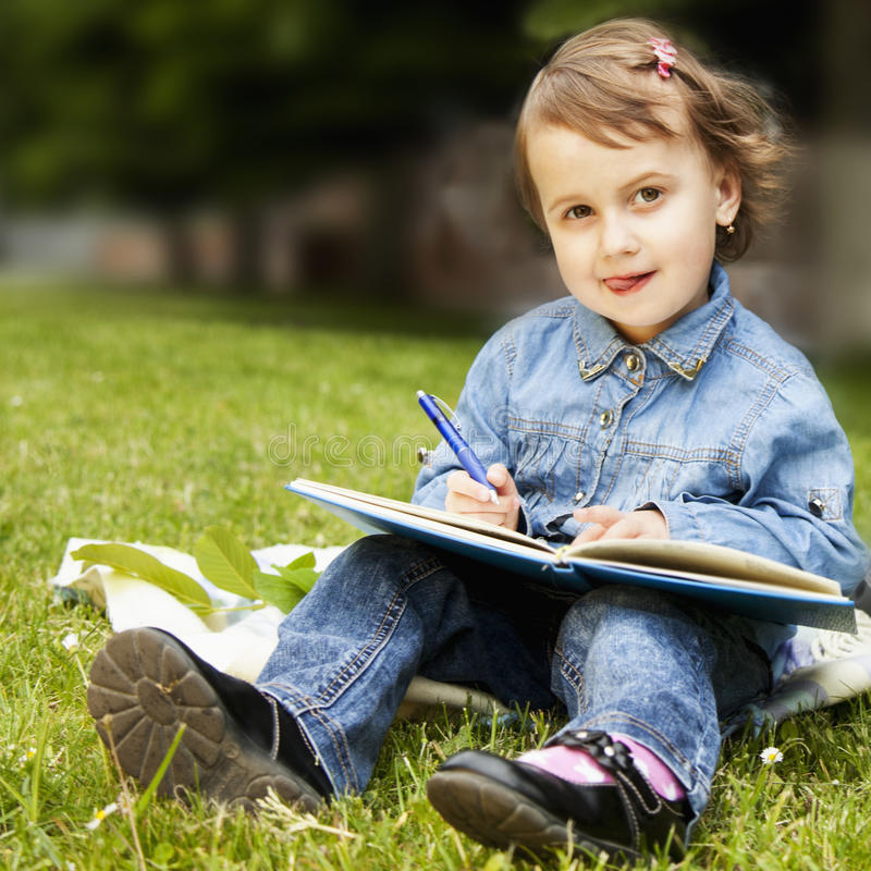 Λίγο κορίτσι επιχειρησιακών παιδιών γράφει στο σημειωματάριο και προγραμματισμός του W της στοκ εικόνες