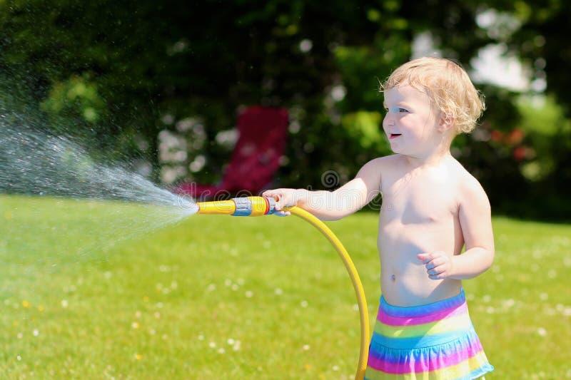 Λίγο κορίτσι μικρών παιδιών που παίζει με τη μάνικα νερού στον κήπο στοκ φωτογραφία με δικαίωμα ελεύθερης χρήσης