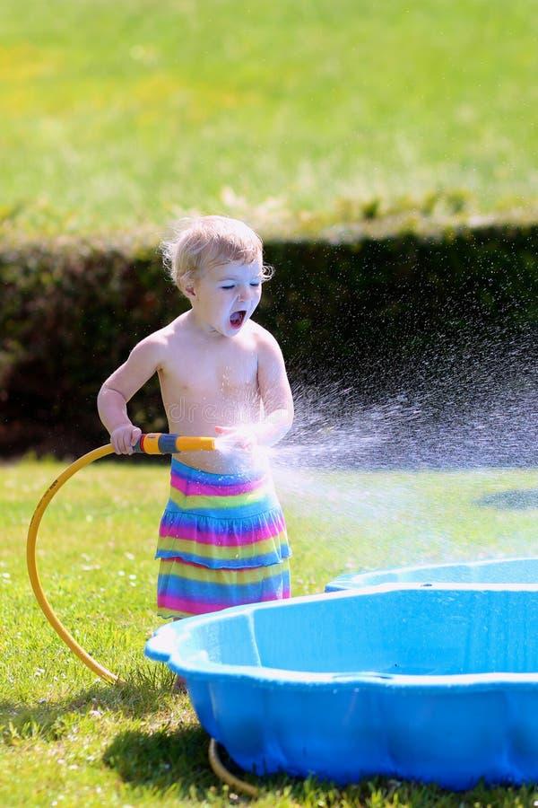 Λίγο κορίτσι μικρών παιδιών που παίζει με τη μάνικα νερού στον κήπο στοκ εικόνα με δικαίωμα ελεύθερης χρήσης
