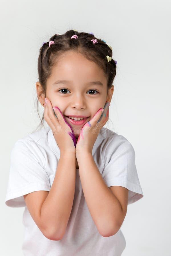 Λίγο κορίτσι παιδιών με τα χέρια χρωμάτισε στο ζωηρόχρωμο χρώμα στοκ εικόνες