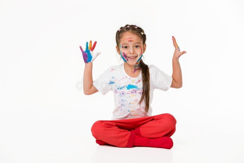 Λίγο κορίτσι παιδιών με τα χέρια χρωμάτισε στο ζωηρόχρωμο χρώμα στοκ φωτογραφία