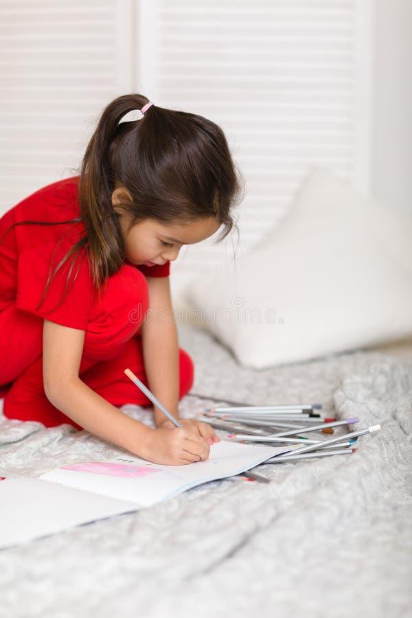 Λίγο κορίτσι παιδιών σύρει με τα μολύβια στο σπίτι στοκ εικόνες