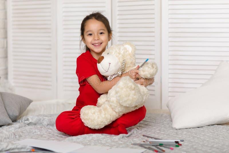 Λίγο κορίτσι παιδιών σύρει με τα μολύβια στο σπίτι στοκ φωτογραφίες