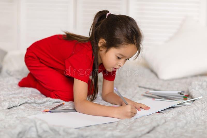 Λίγο κορίτσι παιδιών σύρει με τα μολύβια στο σπίτι στοκ φωτογραφία με δικαίωμα ελεύθερης χρήσης