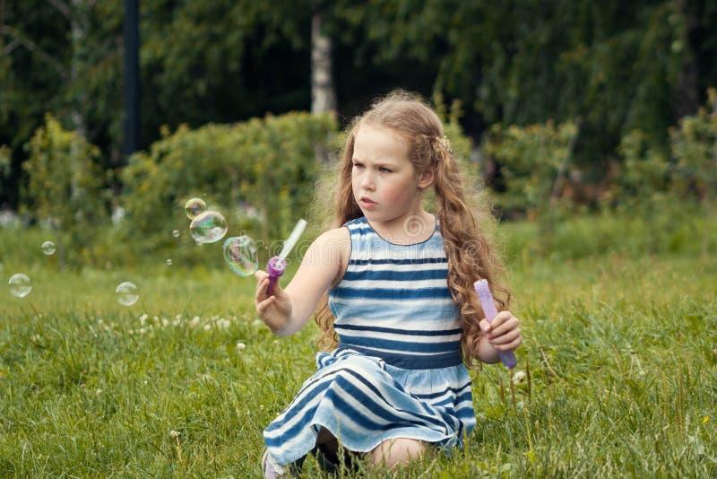 Λίγο κορίτσι παιδιών που παίζει με τη φυσαλίδα σαπουνιών στο θερινό πάρκο στοκ φωτογραφίες με δικαίωμα ελεύθερης χρήσης