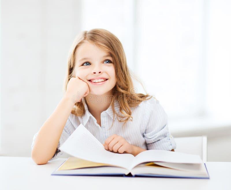 Λίγο κορίτσι σπουδαστών που μελετά στο σχολείο στοκ φωτογραφία