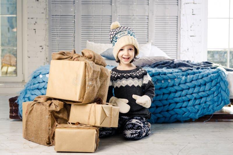 Λίγο κοριτσάκι διπλώνει επάνω ένα βουνό των κιβωτίων δώρων στο σπίτι, κοντά στο κρεβάτι Το εσωτερικό είναι διακοσμημένο με το ντε στοκ εικόνες