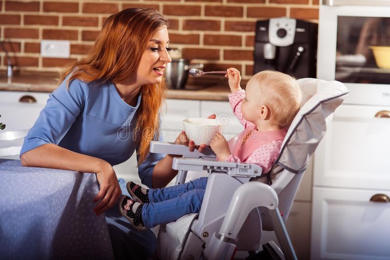 Λίγο κοριτσάκι κάθεται στην υψηλή καρέκλα και σίτιση με το κουτάλι της όμορφης μητέρας της στοκ εικόνες