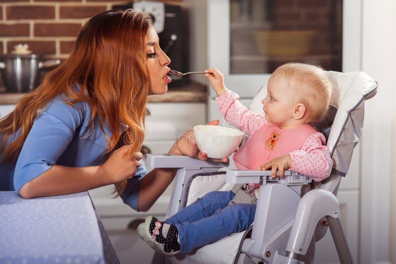 Λίγο κοριτσάκι κάθεται στην υψηλή καρέκλα και σίτιση με το κουτάλι της όμορφης μητέρας της στοκ εικόνα