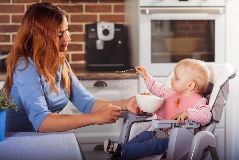 Λίγο κοριτσάκι κάθεται στην υψηλή καρέκλα και αντέχει ένα κουτάλι η όμορφη μητέρα της στοκ φωτογραφίες με δικαίωμα ελεύθερης χρήσης