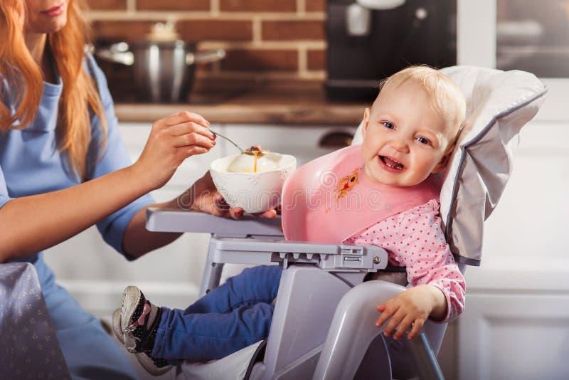 Λίγο κοριτσάκι κάθεται στην υψηλή καρέκλα και σίτιση με το κουτάλι της όμορφης μητέρας της στοκ φωτογραφία