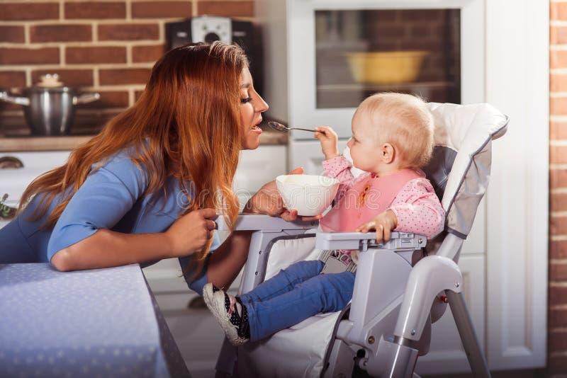 Λίγο κοριτσάκι κάθεται στην υψηλή καρέκλα και σίτιση με το κουτάλι της όμορφης μητέρας της στοκ φωτογραφία με δικαίωμα ελεύθερης χρήσης