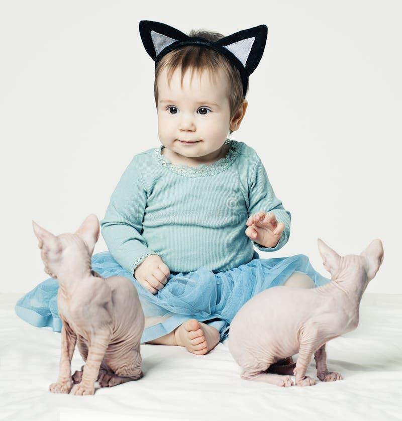 Λίγο κοριτσάκι με δύο γατάκια στο σπίτι στοκ φωτογραφία με δικαίωμα ελεύθερης χρήσης