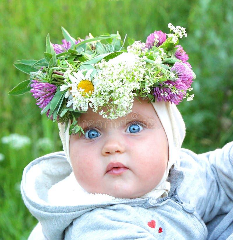 Λίγο κοριτσάκι που φορούν τα λουλούδια και τα χορτάρια στέφουν στο solstice nig στοκ εικόνα