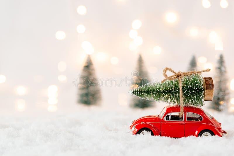 Λίγο κόκκινο φέρνοντας χριστουγεννιάτικο δέντρο παιχνιδιών αυτοκινήτων στοκ εικόνα
