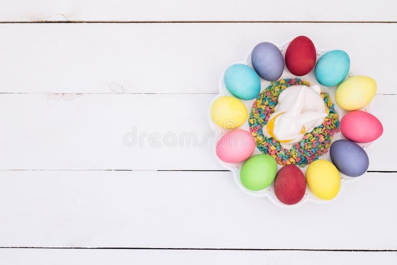 Λίγο λαγουδάκι στο καλάθι με τα διακοσμημένα αυγά Κάρτα Πάσχας Τοπ άποψη με το διάστημα αντιγράφων στοκ εικόνα