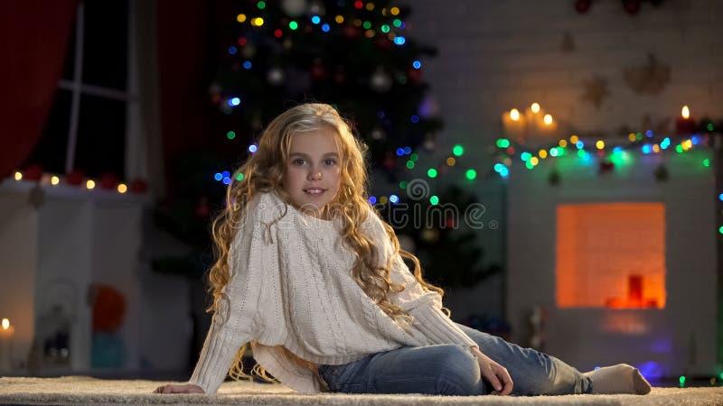 Λίγο λατρευτό κορίτσι στο πάτωμα κάτω από το διακοσμημένο χριστουγεννιάτικο δέντρο, που χαμογελά στη κάμερα στοκ εικόνες με δικαίωμα ελεύθερης χρήσης