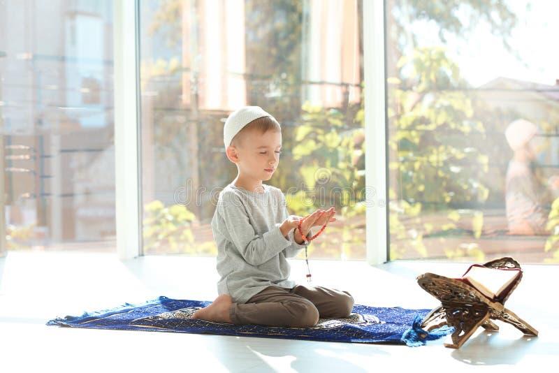 Λίγο μουσουλμανικό αγόρι με το misbaha και Koran που προσεύχεται στην κουβέρτα στοκ εικόνες