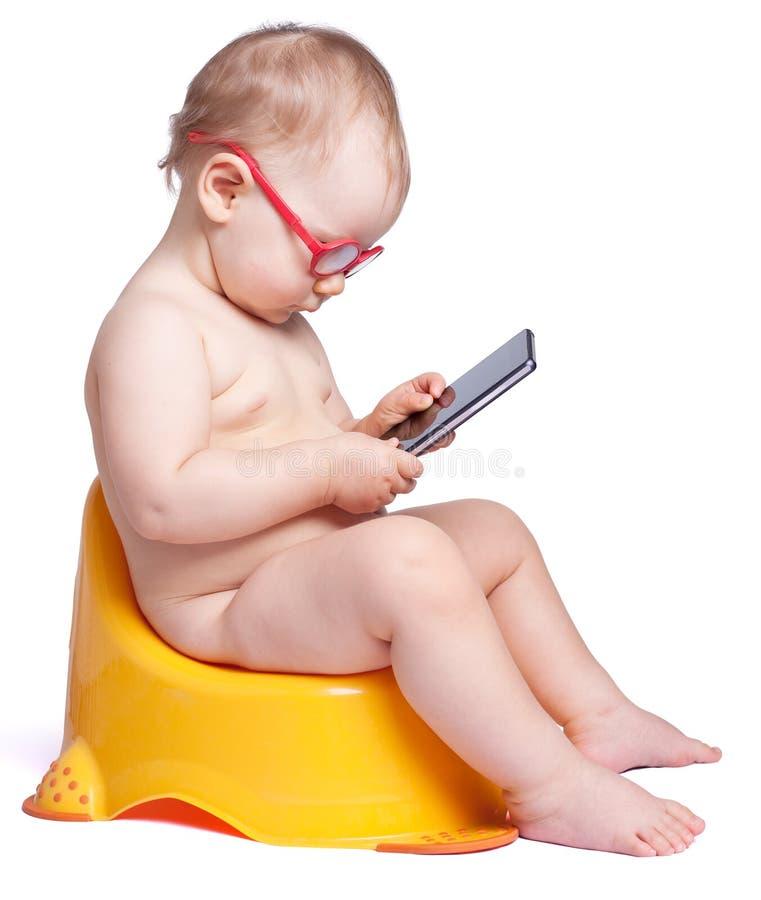 Λίγο μωρό με τα γυαλιά που κάθεται στην τουαλέτα και τα παιχνίδια στο phon στοκ φωτογραφίες