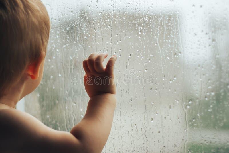 Λίγο μωρό που εξετάζει το παράθυρο με το χέρι βροχής μόνο στοκ εικόνες