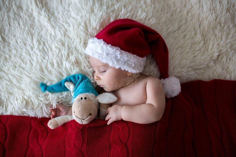 Λίγο νεογέννητο αγοράκι ύπνου, που φορά το καπέλο Santa στοκ εικόνα με δικαίωμα ελεύθερης χρήσης