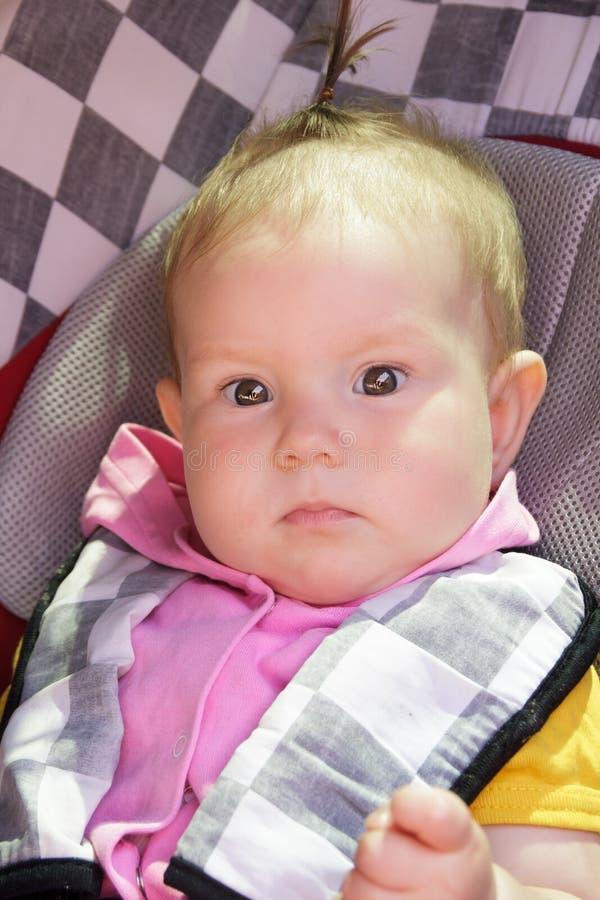 Λίγο νεογέννητο κοριτσάκι στηρίζεται στο κάθισμα αυτοκινήτων στοκ φωτογραφία