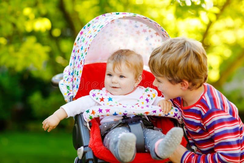 Λίγο ξανθό αγόρι παιδιών που παίζει με την αδελφή μωρών Ευτυχείς αμφιθαλείς στον κήπο Συνεδρίαση κοριτσάκι στο καροτσάκι ή τον πε στοκ φωτογραφίες με δικαίωμα ελεύθερης χρήσης