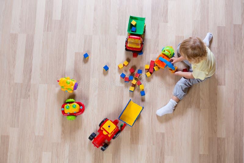 Λίγο ξανθό αγόρι παιδιών που παίζει με τα ζωηρόχρωμα παιχνίδια αυτοκινήτων στη τοπ άποψη πατωμάτων στοκ εικόνα