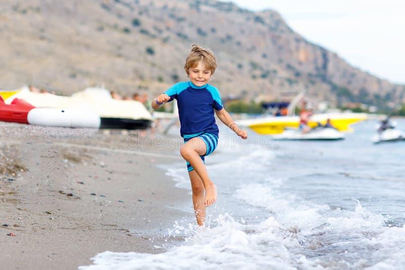 Λίγο ξανθό αγόρι παιδιών που τρέχει την ωκεάνια παραλία στοκ εικόνα