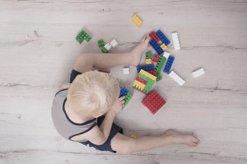 Λίγο ξανθό αγόρι χτίζει του έγχρωμου σχεδιαστή Τοπ όψη στοκ εικόνα