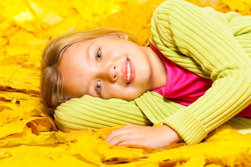 Λίγο ξανθό κορίτσι βάζει στα φύλλα σφενδάμου φθινοπώρου στοκ φωτογραφία