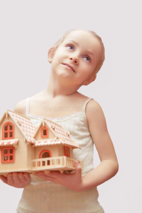 Λίγο ξανθό κορίτσι που ονειρεύεται κρατώντας το μοντέλο κλίμακας του hous στοκ φωτογραφία με δικαίωμα ελεύθερης χρήσης