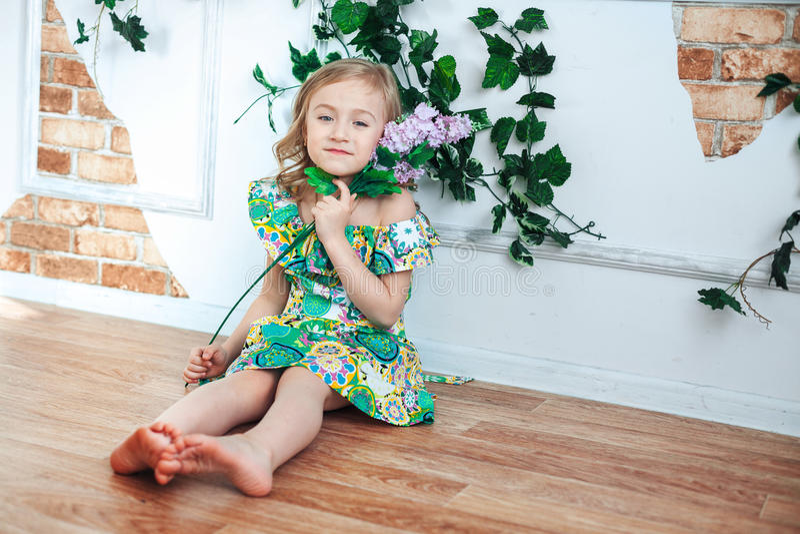 Λίγο ξανθό κορίτσι σε ένα φωτεινό φόρεμα σε ένα δωμάτιο που διακοσμείται με τα λουλούδια στοκ φωτογραφίες με δικαίωμα ελεύθερης χρήσης
