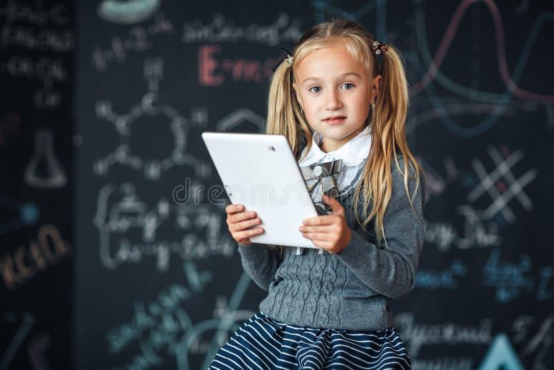 Λίγο ξανθό κορίτσι στη σχολική στολή που κρατά το άσπρο PC ταμπλετών στην κατηγορία χημείας Πίνακας κιμωλίας με το υπόβαθρο σχολι στοκ εικόνες