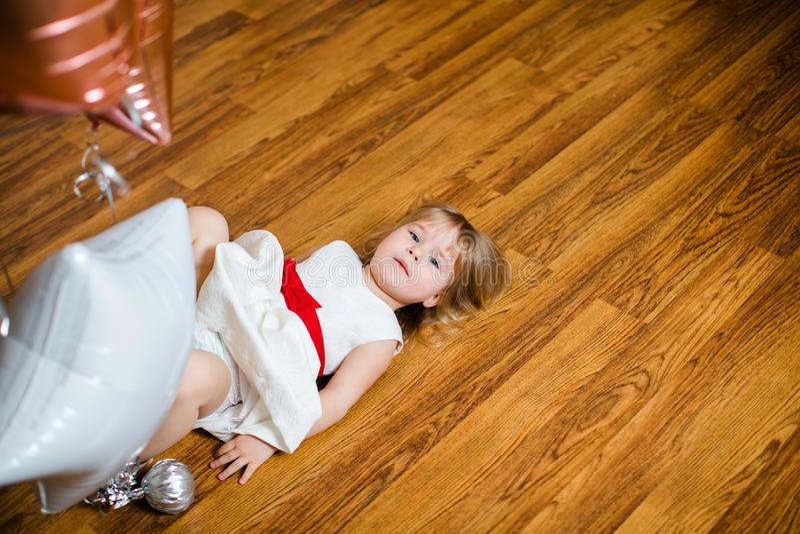 Λίγο ξανθό κοριτσάκι δύο χρονών με τα μεγάλα ρόδινα και άσπρα μπαλόνια που βρίσκονται στο ξύλινο πάτωμα στη γιορτή γενεθλίων της στοκ φωτογραφία