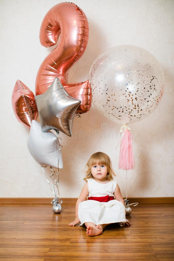 Λίγο ξανθό κοριτσάκι δύο χρονών με τα μεγάλα ρόδινα και άσπρα μπαλόνια στη γιορτή γενεθλίων της στοκ φωτογραφίες