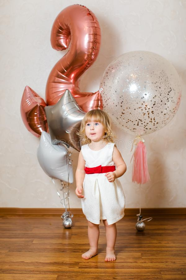 Λίγο ξανθό κοριτσάκι δύο χρονών με τα μεγάλα ρόδινα και άσπρα μπαλόνια στη γιορτή γενεθλίων της στοκ εικόνες με δικαίωμα ελεύθερης χρήσης