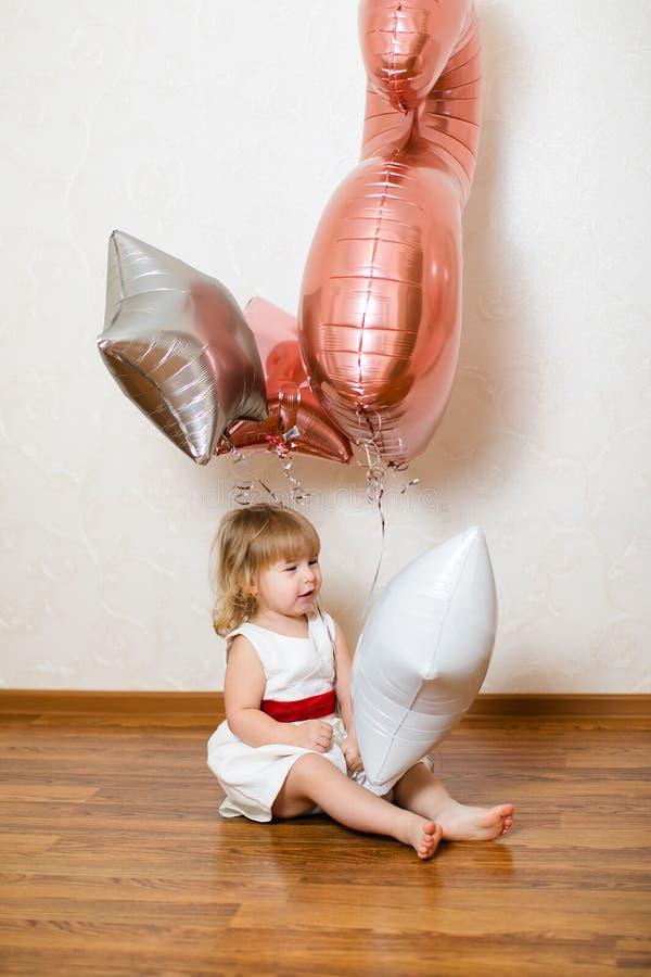 Λίγο ξανθό κοριτσάκι δύο χρονών με τα μεγάλα ρόδινα και άσπρα μπαλόνια στη γιορτή γενεθλίων της στοκ φωτογραφίες με δικαίωμα ελεύθερης χρήσης