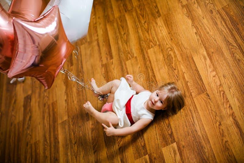 Λίγο ξανθό κοριτσάκι δύο χρονών με τα μεγάλα ρόδινα και άσπρα μπαλόνια που βρίσκονται στο ξύλινο πάτωμα στη γιορτή γενεθλίων της στοκ εικόνες