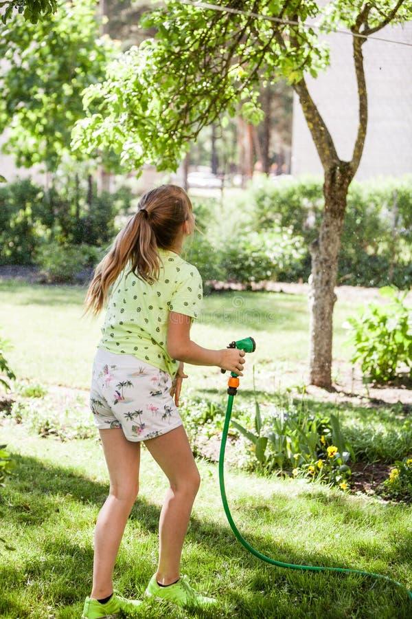 Λίγο παιδί, λατρευτό ξανθό κορίτσι εφήβων, που ποτίζει τις εγκαταστάσεις, όμορφα λουλούδια, από τον ψεκασμό μανικών στον κήπο στοκ φωτογραφία