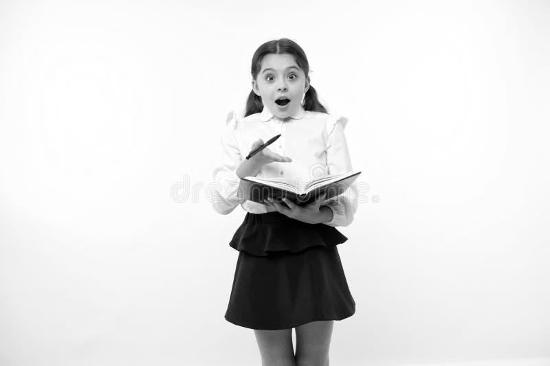 Λίγο παιδί με έκπληκτος κοιτάζει Μαθήτρια με το μακρυμάλλες βιβλίο λαβής με τη μάνδρα Μεγαλοφυία μόδας πίσω σχολείο σπίτι στοκ φωτογραφία
