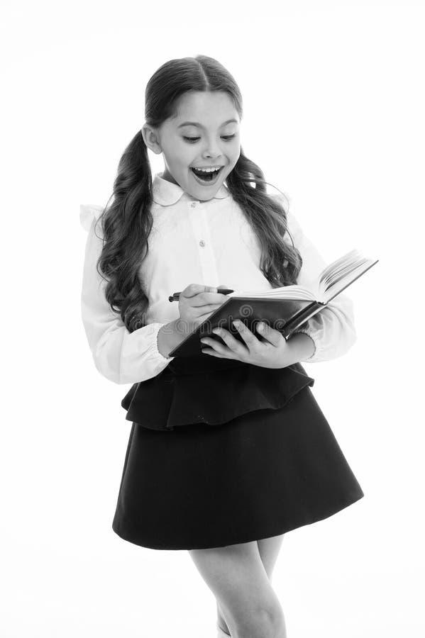 Λίγο παιδί με έκπληκτος φαίνεται απομονωμένο στο λευκό Μαθήτρια με το μακρυμάλλες βιβλίο λαβής με τη μάνδρα κορίτσι στη σχολική σ στοκ φωτογραφία
