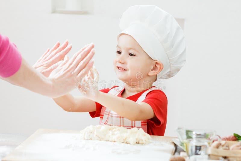 Λίγο παιδί με τη μητέρα που κατασκευάζει τη ζύμη πιτσών ή ζυμαρικών στοκ φωτογραφίες