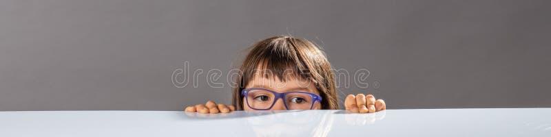 Λίγο παιδί με eyeglasses το κρύψιμο, πάρα πολύ μικρό για να φτάσει στοκ φωτογραφία