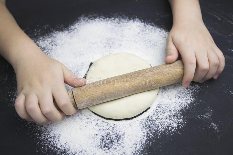 Λίγο παιδί που προετοιμάζει τη ζύμη για την υποστήριξη της πίτας Χέρια παιδιού, κάποιες αλεύρι, ζύμη σίτου και κυλώ-καρφίτσα στο  στοκ εικόνες