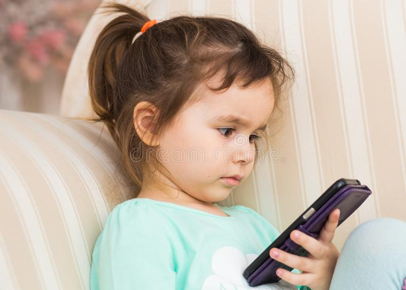 Λίγο παιχνίδι κοριτσιών παιδιών στο smartphone στο σπίτι στοκ φωτογραφία με δικαίωμα ελεύθερης χρήσης
