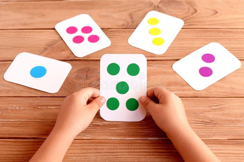 Λίγο παιδί κρατά μια κάρτα κατάρτισης στα χέρια του και εκμάθηση του χρώματος, μορφή, ποσότητα Ζωηρόχρωμες κάρτες λάμψης για το π στοκ εικόνες