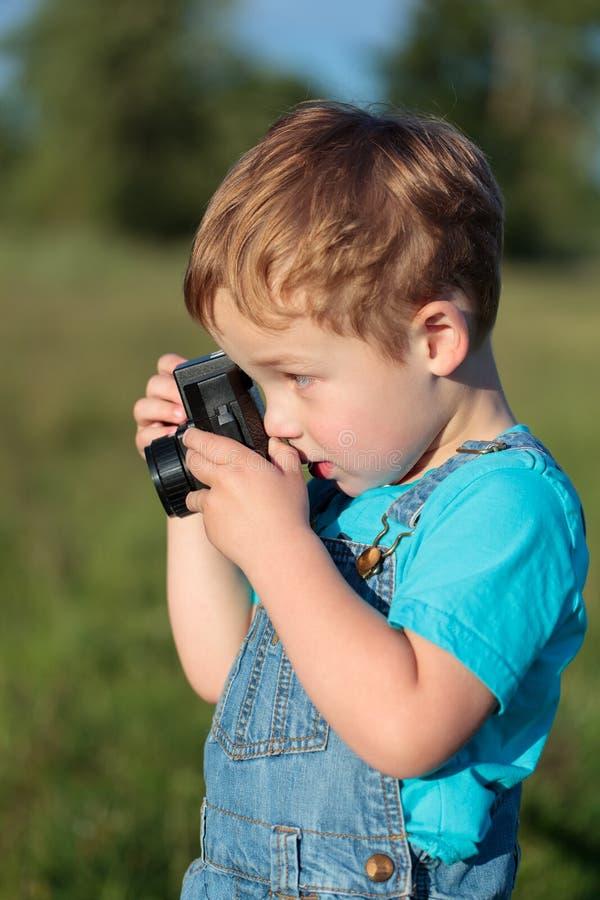 Λίγο παιδί που παίρνει τις εικόνες υπαίθριες στοκ φωτογραφία